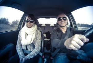 couple with sunglasses driving car merrily