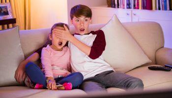 Brother covering surprised sisters eyes watching TV in living room