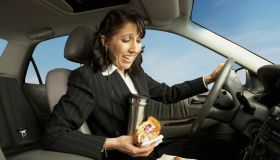 Businesswoman driving and eating