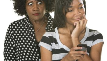 Overprotective mother with teenage daughter reading text messages