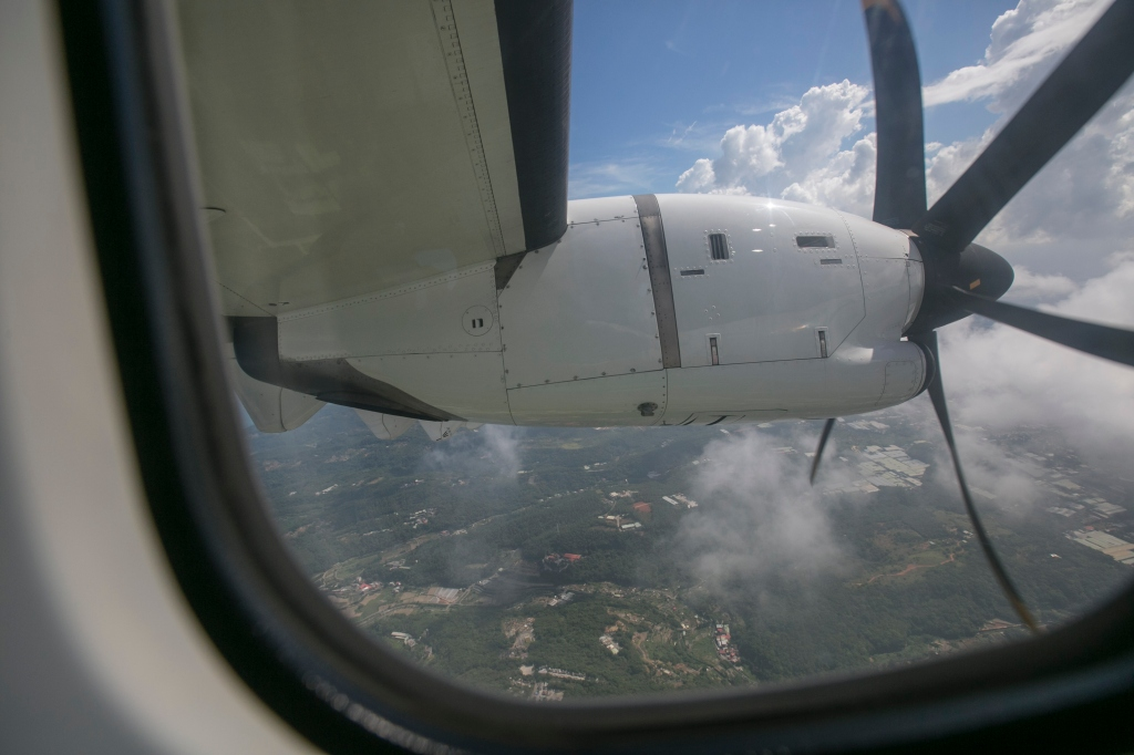 View of Clouds, Land, Sea, Jet Engine and Propeller (with Rolling Shutter) Through Airplane Window