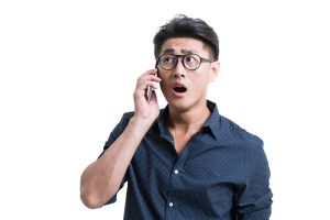 Shocked young man talking on cell phone