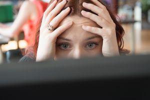Frustrated Caucasian businesswoman using computer