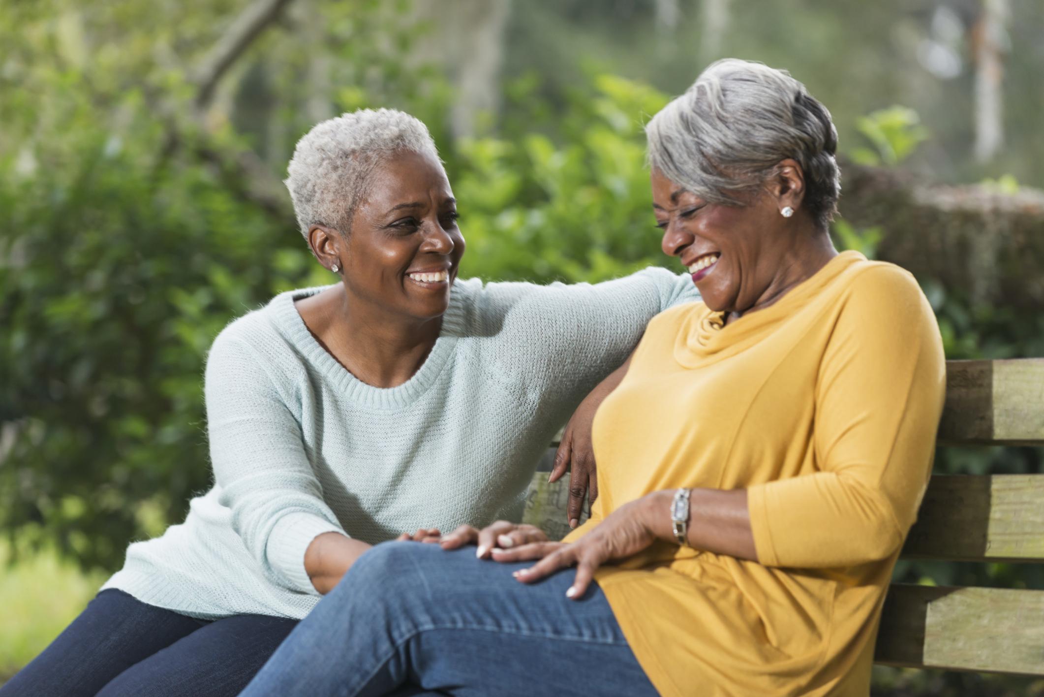 Two senior women sitting on park bench laughing