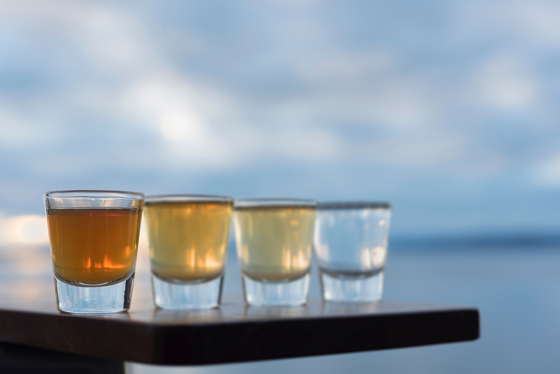Tequila Shots On Table By Sea Against Sky