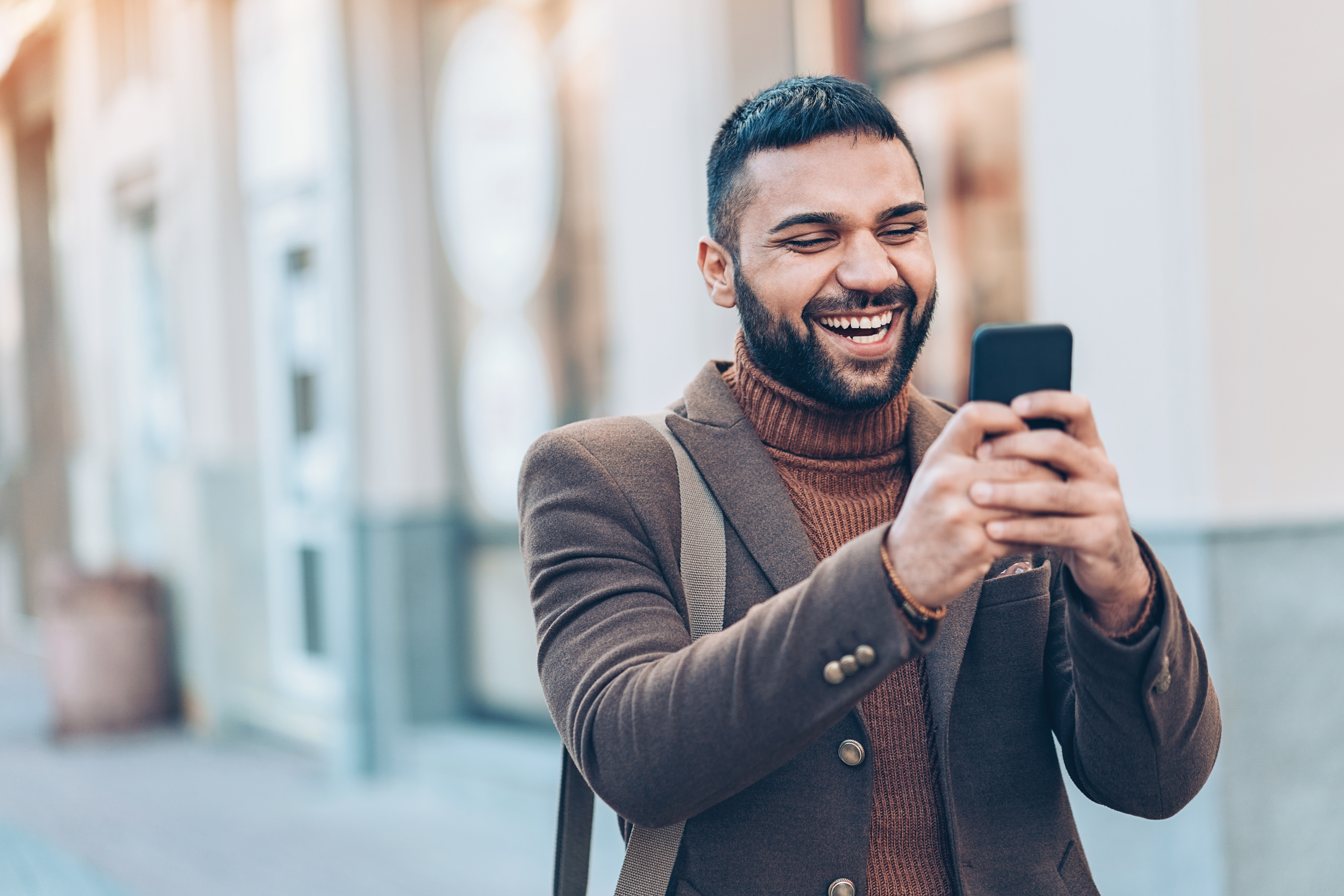 Smiling man with smart phone outdoors in the city