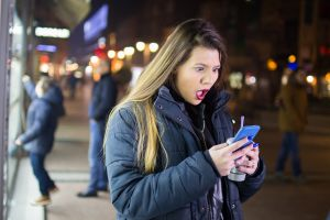 Girl downtown at night using phone
