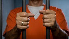 A prisoner standing behind prison bars