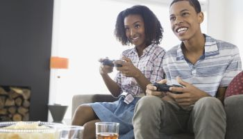 Siblings playing video games at home