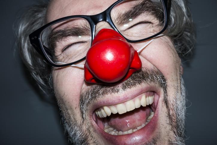 Laughing man wearing a red nose