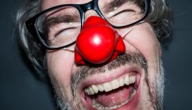 Laughing man wearing a red nose