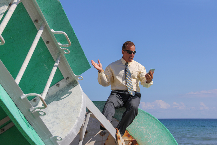 Businessman looking at mobile phone drifting on a buoy out at sea