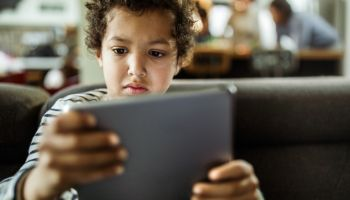 Small black boy watching cartoons on touchpad at home.